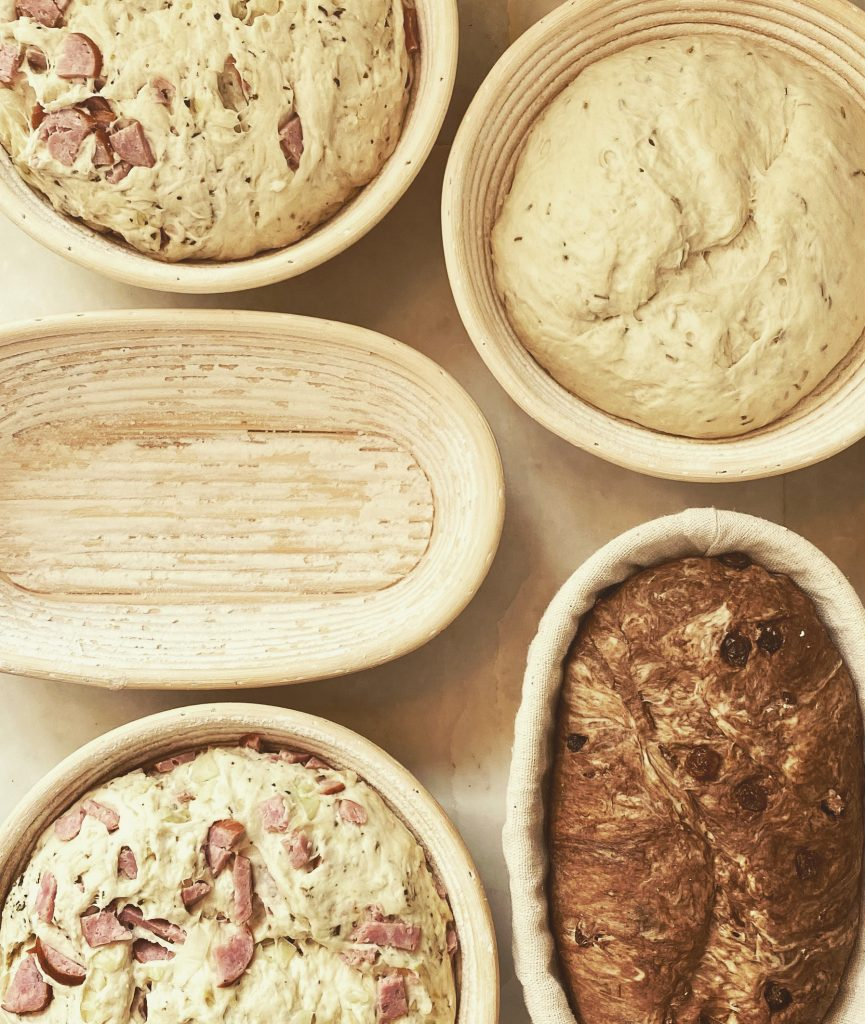 4 shaped doughs proofing in baskets 1 floured empty basket